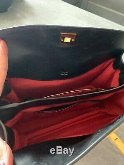 Sac à main Lancel modèle Pia en cuir noir lisse doublé rouge